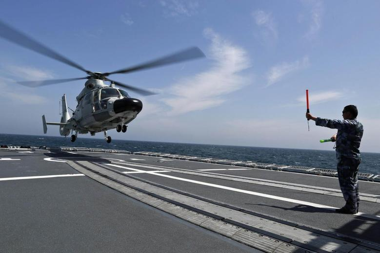 A Chinese navy sailor (R) guides a helicopter to land on Chinese destroyer Harbin during the Joint Sea-2014 naval drill outside Shanghai on the East China Sea, May 24, 2014. REUTERS/China Daily