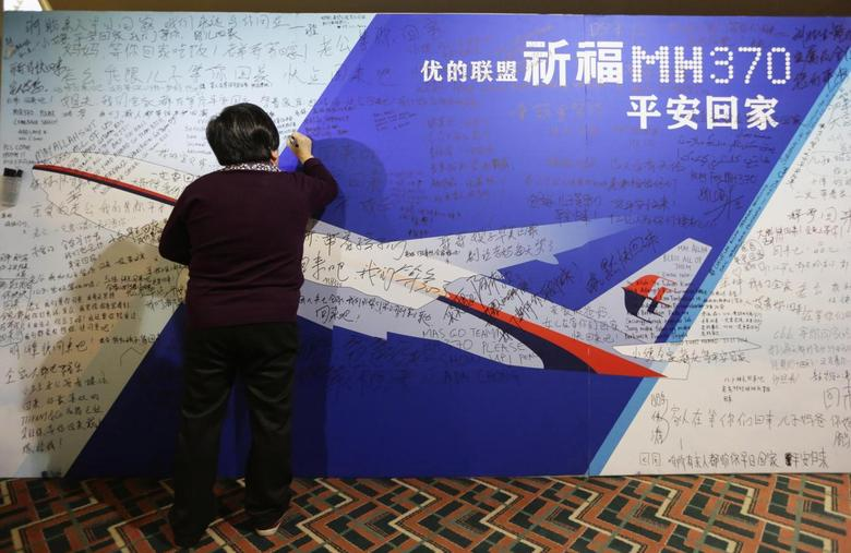 A mother writes a message to her son on a board dedicated to passengers onboard the missing Malaysia Airlines Flight MH370 at Lido Hotel, in Beijing March 24, 2014.  REUTERS/Jason Lee