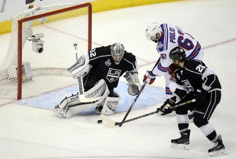 Jun 7, 2014; Los Angeles, CA, USA; Los Angeles Kings goalie Jonathan Quick (32) makes a save as defenseman Slava Voynov (26) tries to clear the puck away from New York Rangers left wing Benoit Pouliot (67) in the second period during game two of the 2014 Stanley Cup Final at Staples Center. Mandatory Credit: Richard Mackson-USA TODAY Sports
