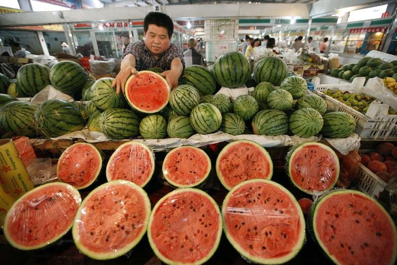 A fruit vendor arranges watermelons at a market in Huaibei, Anhui province June 10, 2014. REUTERS/Stringer