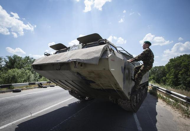 A pro-Russian separatist climbs on amphibious vehicle near a road check point outside the eastern Ukrainian city of Luhansk June 8, 2014. REUTERS/Shamil Zhumatov