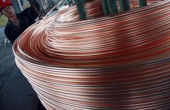 En la imagen un empleado enrrolla cables de cobre en una fábrica en Nantong, 18 de junio de 2014. El cobre tocó mínimos de un mes el martes, debido a que una investigación sobre irregularidades en el financiamiento de operaciones con metales en China generó preocupaciones de que una crisis podría afectar el comercio del metal.  REUTERS/China Daily
