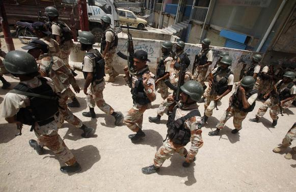 Paramilitary soldiers march along a street in a neighbourhood after a gunfire attack on a security academy run by the Airports Security Force (ASF) in Karachi June 10, 2014. REUTERS/Athar Hussain