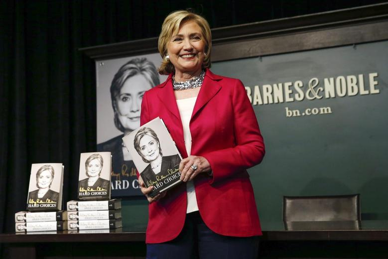 Hillary Clinton poses with her new book ''Hard Choices'' during a book signing in New York June 10, 2014.  REUTERS/Shannon Stapleton