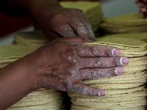 Una mujer arregla tortillas en una tienda en Ciudad de México, ene 5 2011. La productora mexicana de tortillas y harina de maíz Gruma dijo el martes que llegó a un acuerdo para vender en 200 millones de dólares sus operaciones de harina de trigo en México a Grupo Trimex, como parte de su estrategia para enfocarse a su negocio principal.    REUTERS/Henry Romero