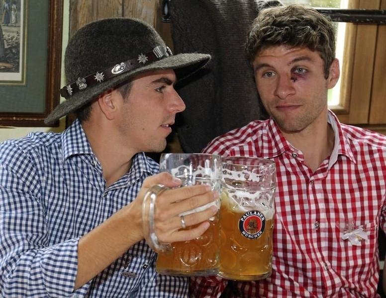 Bayern Munich's Philipp Lahm and Thomas Mueller salute at the Oktoberfest in Munich October 7, 2012.  REUTERS/Thomas Niedermueller/Pool/Files
