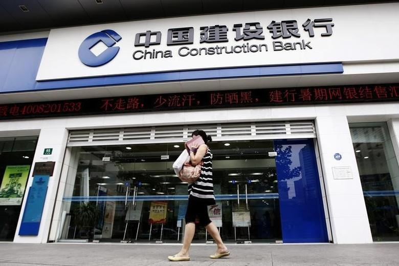 A woman walks past a branch of the China Construction Bank (CCB) in Shanghai, August 26, 2013.  REUTERS/Aly Song
