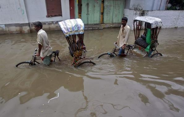 Rickshaw riders make their way through a flooded road after a heavy rain shower in Agartala, capital of Tripura June 11, 2014. REUTERS/Jayanta Dey