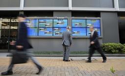 Un hombre mira el promedio del Nikkei japonés y varios valores de otros países afuera de la bolsa de Tokyo, 16 de abril de 2014. Las bolsas en Asia caían el jueves luego de que un retroceso en Wall Street y una escalada de la violencia en Irak mermaron el apetito por el riesgo, lo que a su vez mantenía los precios del petróleo cerca de unos máximos en tres meses. REUTERS/Toru Hanai