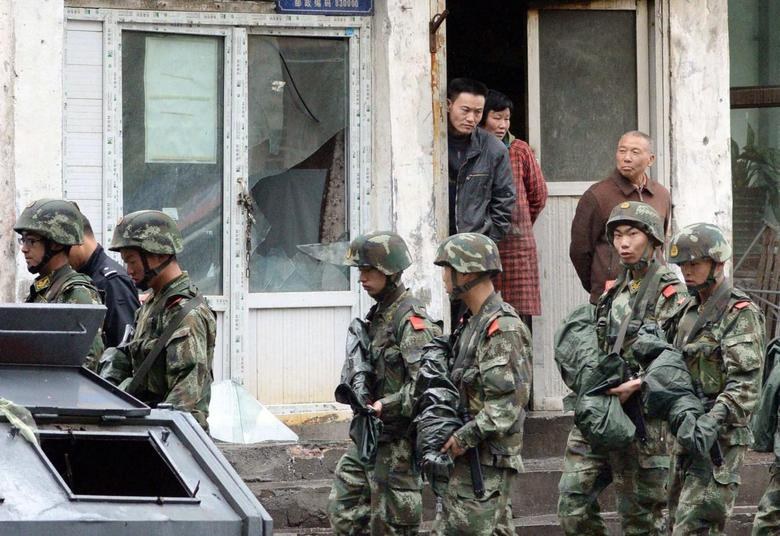 Paramilitary policemen patrol past a building, where a window was damaged by an explosion in Urumqi on Thursday, in the Xinjiang Uighur Autonomous Region, in this photo taken by Kyodo on May 22, 2014.  REUTERS/Kyodo