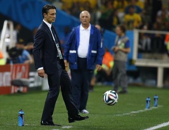 Croatia's coach Niko Kovac (L) kicks a soccer ball as Brazil's coach Luiz Felipe Scolari looks on during their 2014 World cup opening match between Brazil and Croatia at the Corinthians arena in Sao Paulo June 12, 2014. REUTERS/Kai Pfaffenbach