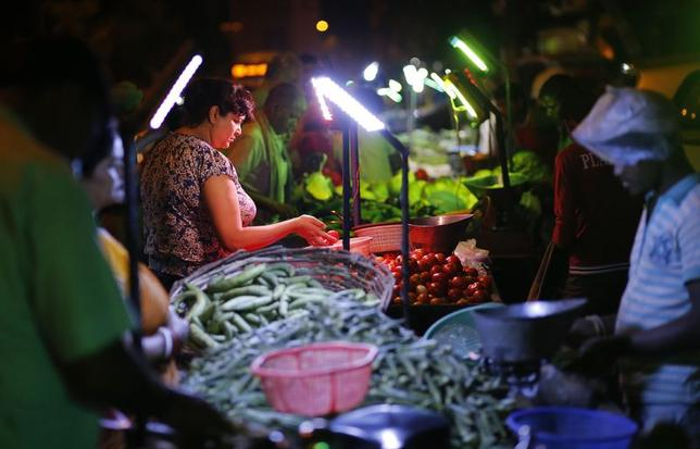 Customers shop at an open air evening vegetable and fruit market illuminated by battery powered lights due to a power cut in New Delhi June 12, 2014. REUTERS/Anindito Mukherjee/Files