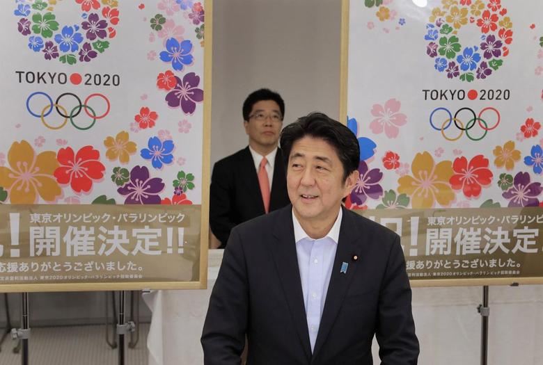 Japan's Prime Minister Shinzo Abe smiles as he reports to his cabinet members Tokyo's successful bid to host the 2020 Summer Olympics and Paralympics at the IOC meeting after returning from Buenos Aires, Argentina, during a cabinet meeting at the prime minister's official residence in Tokyo in this September 10, 2013 file photo. REUTERS/Itsuo Inouye/Pool/Files