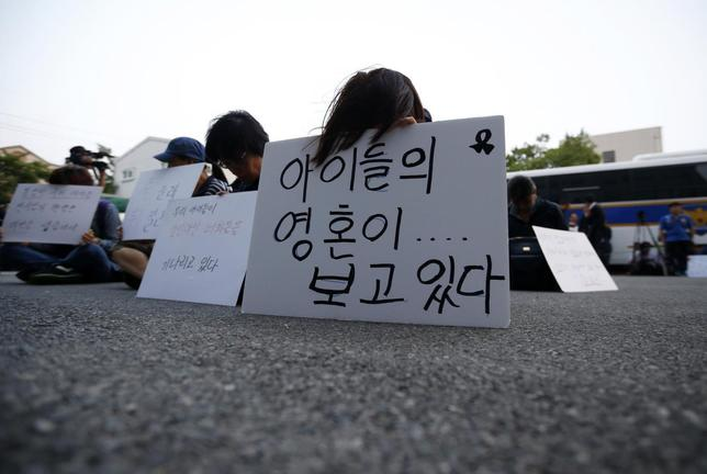 Family members of victims onboard sunken ferry Sewol sit in front of a building in which crew members are detained, after attending a hearing at the local court in Gwangju June 10, 2014. REUTERS/Kim Hong-Ji