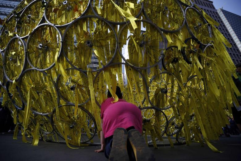 A boy looks inside a installation art dedicated to the dead and missing people onboard sunken ferry Sewol before a candlelight rally to mourn victims of sunken ferry Sewol and denounce the government's handling of the disaster in central Seoul May 17, 2014. REUTERS/Kim Hong-Ji