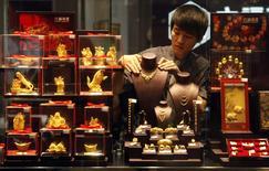 Imagen de un empleado ajustando un collar de oro en una estatuilla en una tienda de oro en Wuhan, 11 de junio de 2014.  El oro cotizaba estable el viernes, recibiendo cierto apoyo de la debilidad de las acciones luego de que el Banco de Inglaterra planteara la posibilidad de un alza en las tasas de interés, mientras que la violencia en Irak podría realzar el atractivo del metal como cobertura contra el riesgo.. REUTERS/Stringer