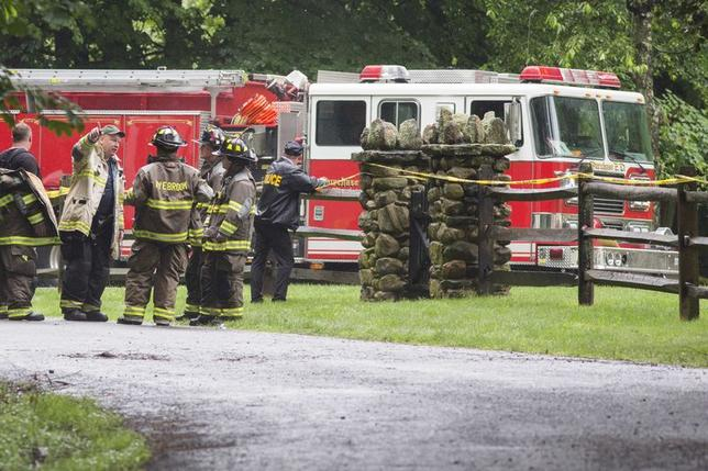 Police and firefighters stand near the site of a small plane crash in the town of Harrison, Westchester County, New York June 13, 2014.  REUTERS/Adrees Latif