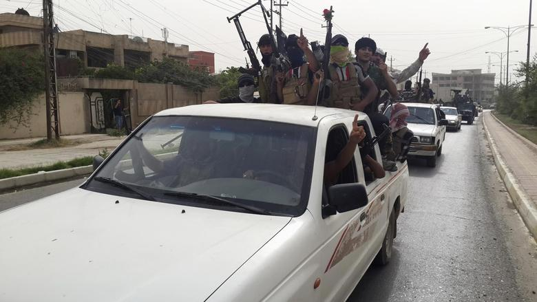 Fighters of the Islamic State of Iraq and the Levant (ISIL) celebrate on vehicles taken from Iraqi security forces, at a street in city of Mosul, June 12, 2014. REUTERS/Stringer