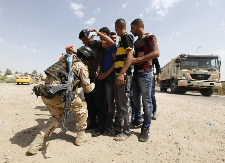 A member of Iraqi security forces searches volunteers who have joined the Iraqi Army to fight against predominantly Sunni militants, who have taken over Mosul and other Northern provinces, before they board an army truck in Baghdad, June 13, 2014.  REUTERS/Ahmed Saad