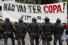Police officers stand guard in front of a banner during a protest against the 2014 World Cup in Rio de Janeiro June 12, 2014.  REUTERS/Marcelo Regua