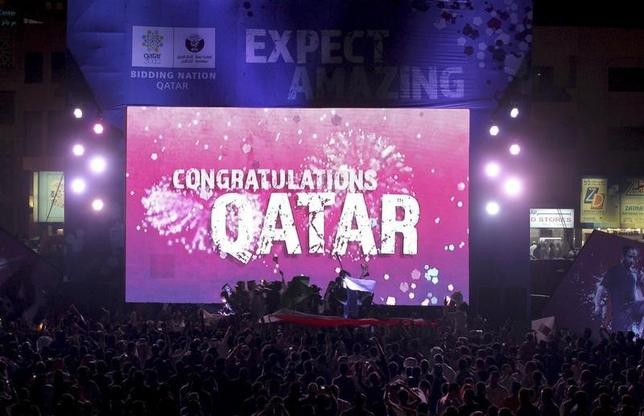 People celebrate in front of a screen that reads ''Congratulations Qatar'' after FIFA announced that Qatar will be host of the 2022 World Cup in Souq Waqif in Doha, December 2, 2010. REUTERS/Fadi Al-Assaad/Files