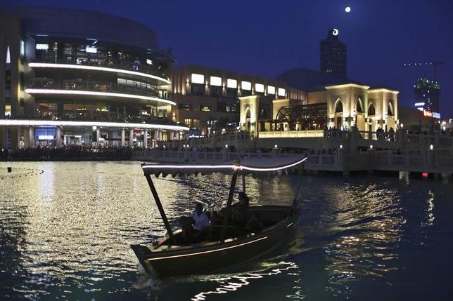 People travel on a boat in an artificial lake at Dubai Mall area in Dubai March 15, 2014. REUTERS/Ahmed Jadallah/Files