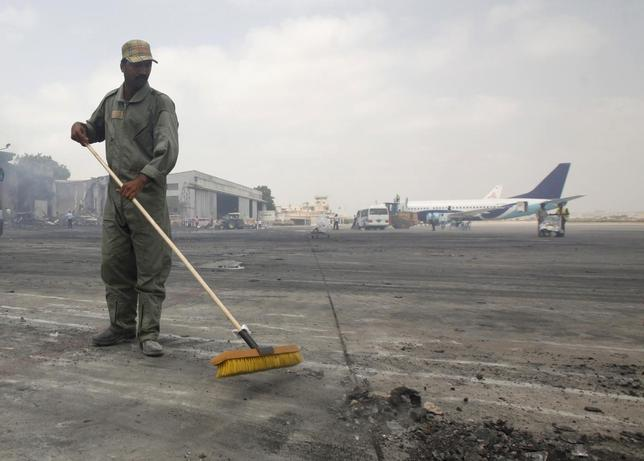 A man clears debris from the tarmac of Jinnah International Airport, after Sunday's attack by Taliban militants on Sunday, in Karachi June 10, 2014. REUTERS/Athar Hussain