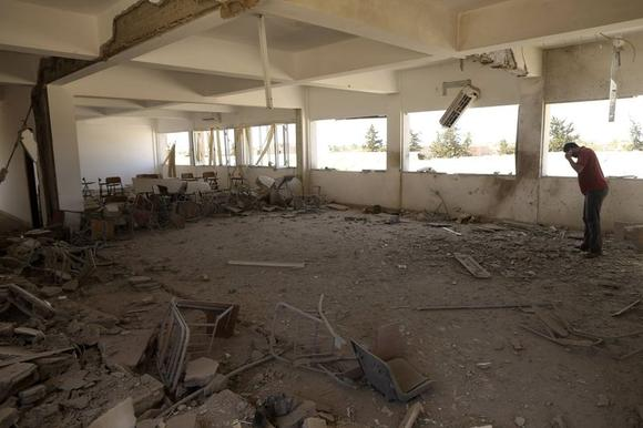 A teacher stands inside a damaged classroom after the building was bombed by a Libyan warplane at a university in Benghazi June 1, 2014.  REUTERS/Esam Omran Al-Fetori
