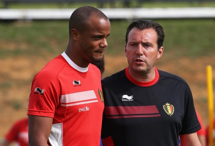 Belgium's national soccer coach Marc Wilmots talks with his player Vincent Kompany (R) during a training session in Mogi das Cruzes, near Sao Paulo June 14, 2014.  REUTERS/Nacho Doce