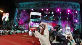 Los proveedores de procesadores para los fabricantes de teléfonos móviles avanzados han dado un paso inusual al ayudar a sus clientes a conseguir otros componentes como altavoces o lentes de cámaras en un intento para ganar mercado en un sector cada vez más competitivo. En la imagen, gente grabando con sus teléfonos inteligentes durante la inauguración del 22º Life Ball, en Viena, el 31 de mayo de 2014. REUTERS/Leonhard Foeger