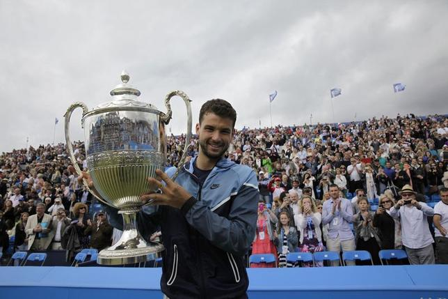 Bulgaria's Grigor Dimitrov celebrates with the trophy after defeating Spain's Feliciano Lopez in their men's singles final tennis match at the Queen's Club Championships in west London June 15, 2014. REUTERS/Stefan Wermuth