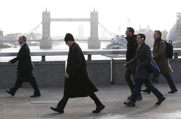 Tower Bridge is seen behind commuters as they walk across London Bridge during an Underground strike in London February 5, 2014. REUTERS/Eddie Keogh/Files