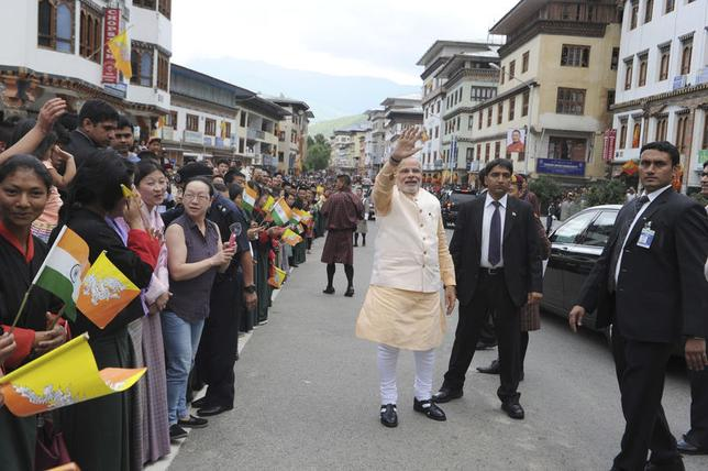 Prime Minister Narendra Modi (C) waves to the Bhutanese people in Thimphu before making his way to the airport, June 16, 2014. REUTERS/India's Press Information Bureau/Handout via Reuters
