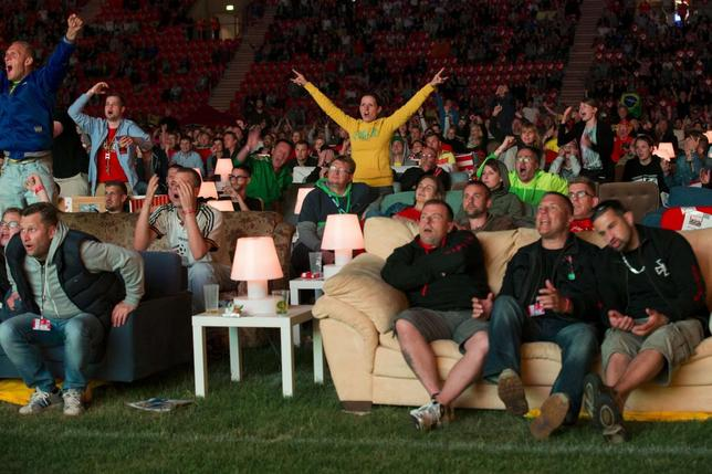 People react as Brazil scores against Croatia during a public viewing of the opening game of the 2014 World Cup at the Alte Foersterei stadium in Berlin, June 12, 2014.  REUTERS/Thomas Peter
