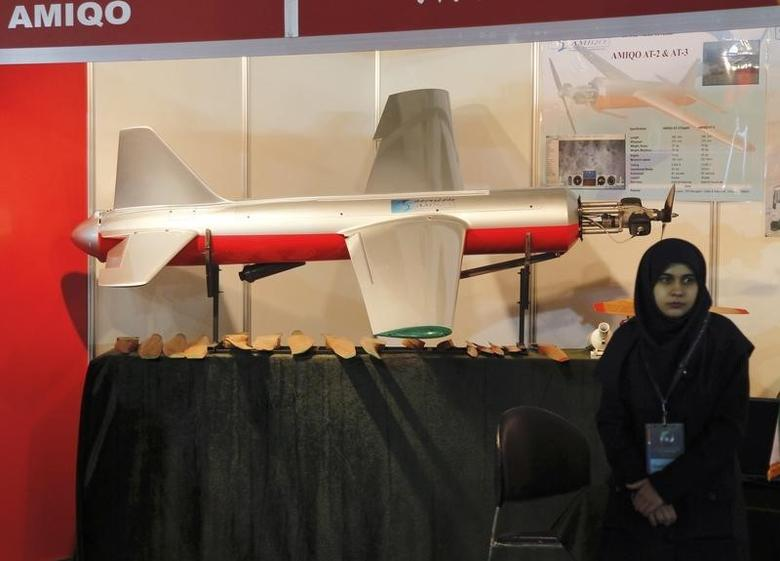 An Iranian exhibitor stands beside an unmanned drone aircraft during Iran's Hi-Tech Expo opening at the Fairgrounds, near Damascus, February 9, 2011. REUTERS/Khaled al-Hariri