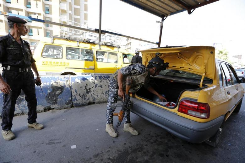 A member of the Iraqi security forces searches the trunk of a vehicle at a checkpoint, as security increases in Baghdad, June 16, 2014.  REUTERS/Thaier Al-Sudani