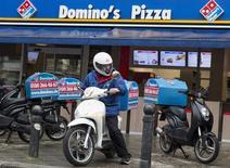 """Un repartidor de Domino's Pizza a las afueras de un local de la firma en Berlín, ago 23 2013. Piratas informáticos robaron datos de más de 600.000 clientes de Dominos Pizza en Bélgica y Francia, dijo la empresa de reparto de pizzas, y un usuario anónimo de Twitter amenazó con hacer pública la información a menos que la compañía pague un monto de """"rescate"""" en efectivo.   REUTERS/Thomas Peter"""