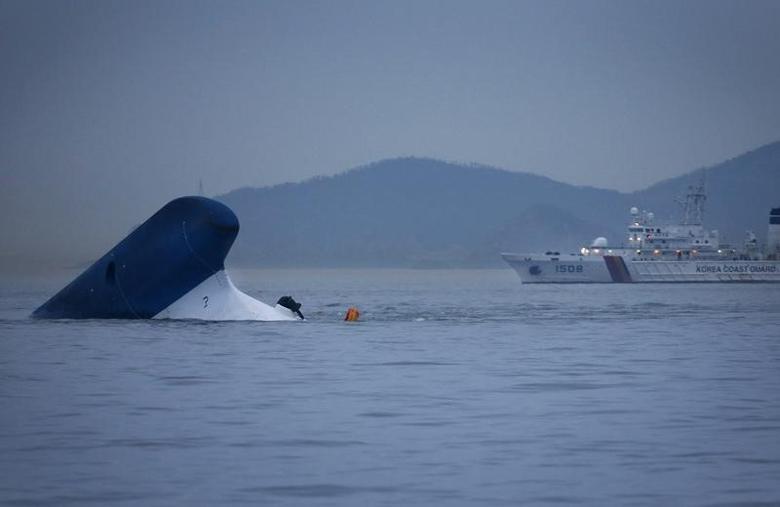 A Coast Guard ship passes near the upturned South Korean ferry ''Sewol'' in the sea off Jindo April 16, 2014. REUTERS/Kim Hong-Ji