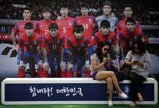 Женщины у плаката сборной Южной Кореи в Сеуле, 17 июня 2014 года. REUTERS/Kim Hong-Ji