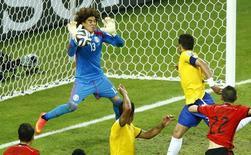 Goleiro mexicano Ochoa defende cabeceio de Thiago Silva.  REUTERS/Mike Blake