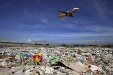 An aircraft flies overhead as a person rummages for recyclables at a garbage dumpsite in Paranaque city, metro Manila in this June 8, 2014 file photo. REUTERS/Romeo Ranoco/Files