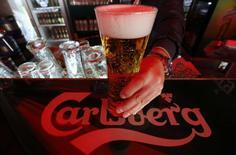 Бармен держит в руках бокал пива Carlsberg в баре в Санкт-Петербурге 17 июня 2014 года.  Датская пивоваренная компания Carlsberg не собирается останавливать заводы в России, даже учитывая, что большинство из них не работают на полную мощность, тогда как некоторые западные пивовары закрывают производство в РФ из-за санкций Запада, недовольного вмешательством России в дела Украины. REUTERS/Alexander Demianchuk