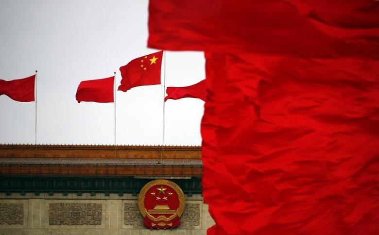 Red flags flutter next to a national emblem and a national flag of China on top of the Great Hall of the People, which is the venue of the closing ceremony of the Chinese People's Political Consultative Conference (CPPCC), in Beijing, March 12, 2014. REUTERS/Petar Kujundzic