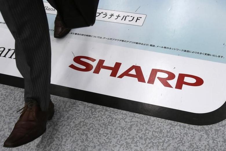 A man walks past an advertisement of Sharp Corp at an electronics retail store in Tokyo October 31, 2013.    REUTERS/Toru Hanai