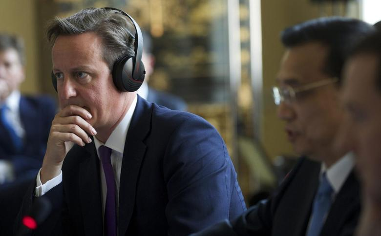 Britain's Prime Minister David Cameron listens to proceedings translated through headphones as Chinese Premier Li Keqiang (2nd L) speaks during a global economic roundtable in Downing street, London June 17, 2014. REUTERS/Andrew Cowie/Pool