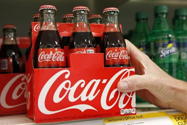 An employee arranges bottles of Coca-Cola at a store in Alexandria, Virginia October 16, 2012.  REUTERS/Kevin Lamarque