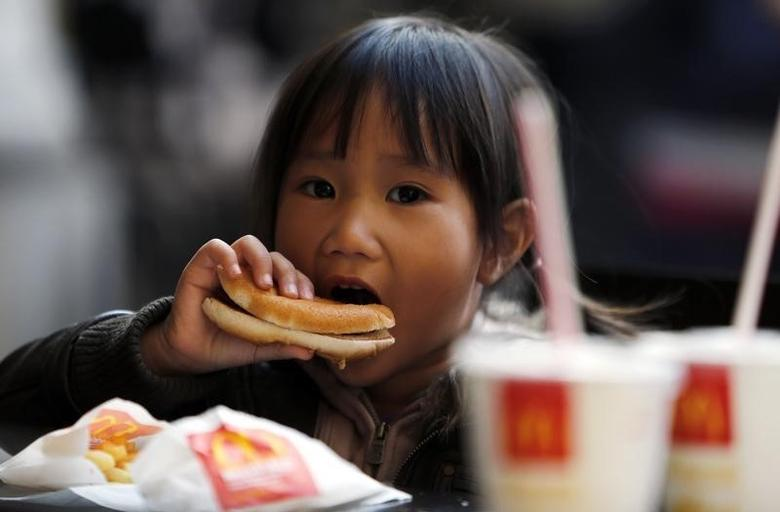 A child eats a hamburger outside a McDonald's fast food restaurant in downtown Milan October 16, 2012. REUTERS/Stefano Rellandini