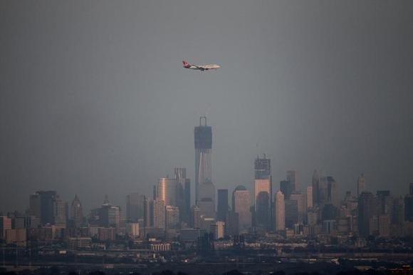 An airplane flies past the haze covered skyline of New York's Lower Manhattan as seen from the Eagle Rock Reservation in West Orange, New Jersey, August 31, 2012. REUTERS/Gary Hershorn