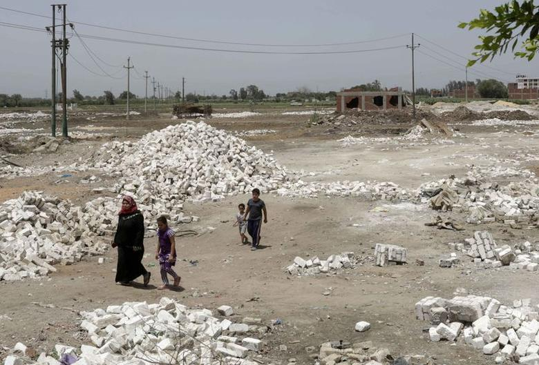 Residents walk near illegal buildings built on farmland at the Qalubiya town of Kaha, about 50 km (30 miles) north of Cairo June 16, 2014. REUTERS/Asmaa Waguih
