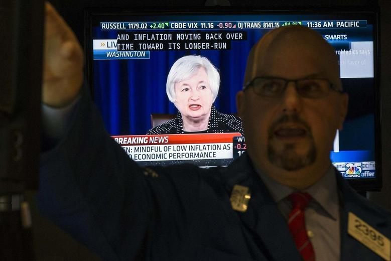 A television screen displays Federal Reserve Chair Janet Yellen's news conference as specialist John Urbanowicz works on the floor of the New York Stock Exchange June 18, 2014.    REUTERS/Brendan McDermid